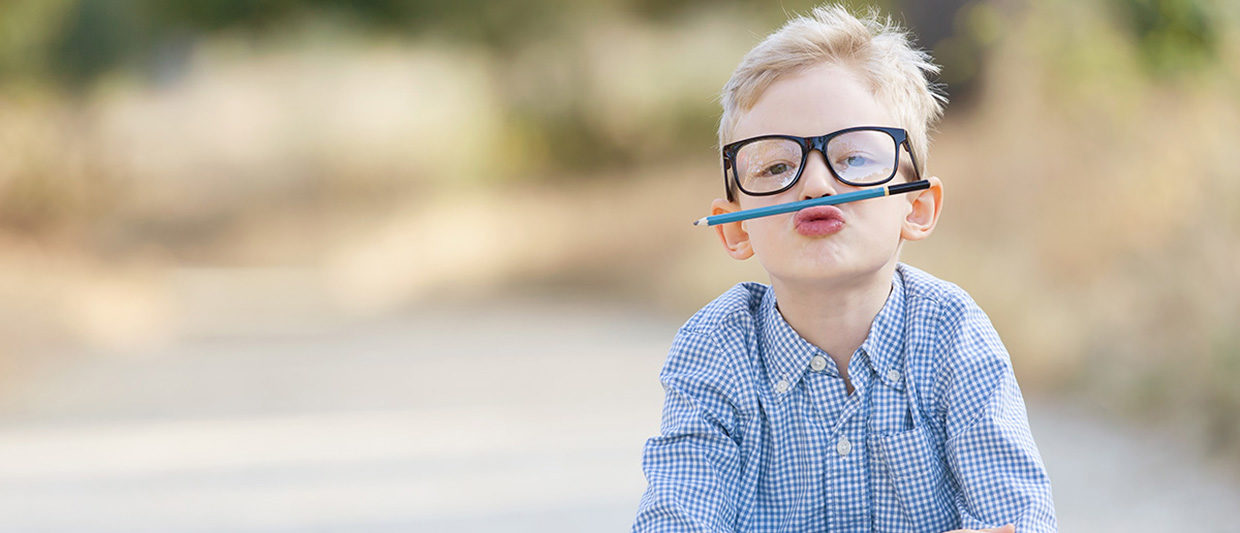 Boy holding pencil under nose and wearing glasses