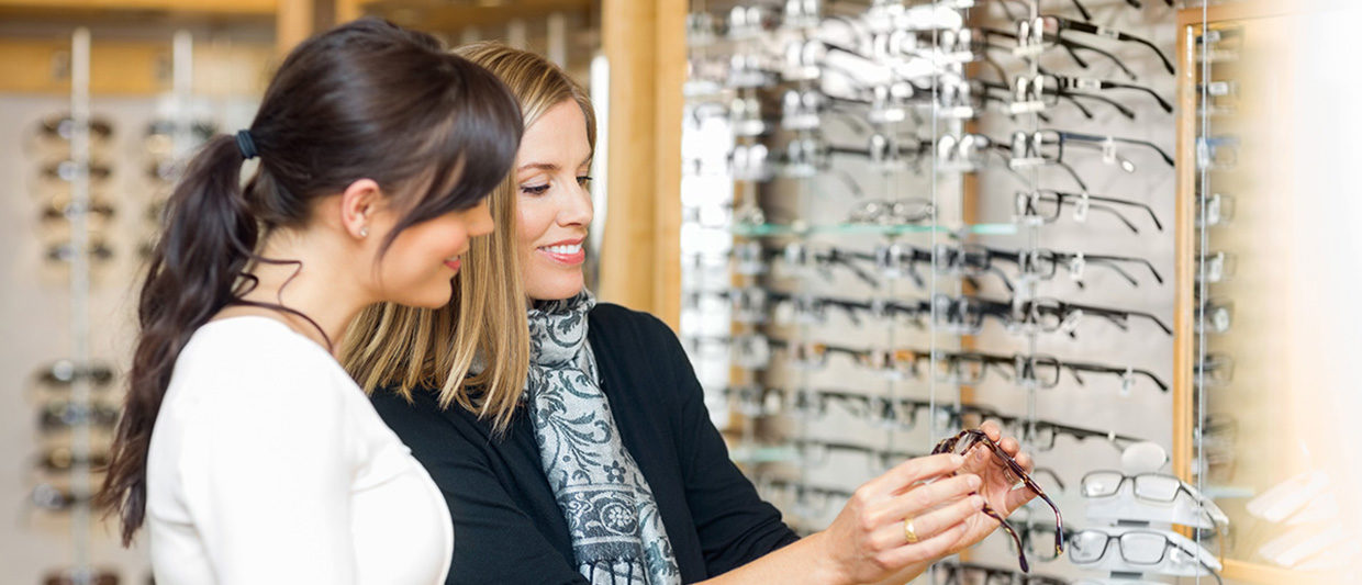 woman trying on glasses frames with a friend